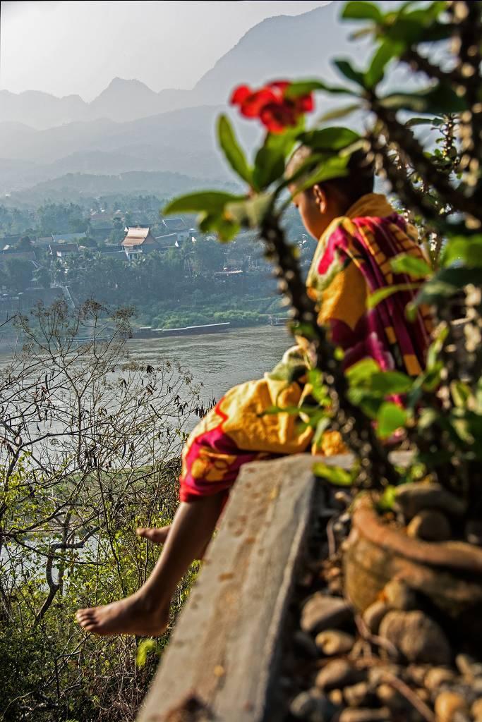 Prime luci del giorno per il giovane monaco affacciato al Nam Khan